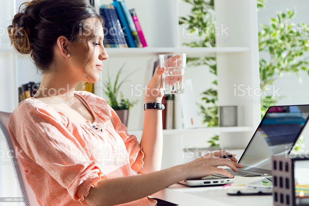 Beautiful young woman working with her laptop at home. stock photo
