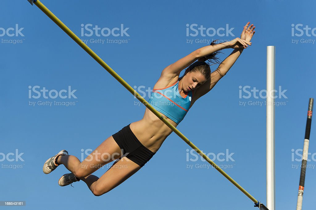 Beautiful young women at successful jump over the lath royalty-free stock photo