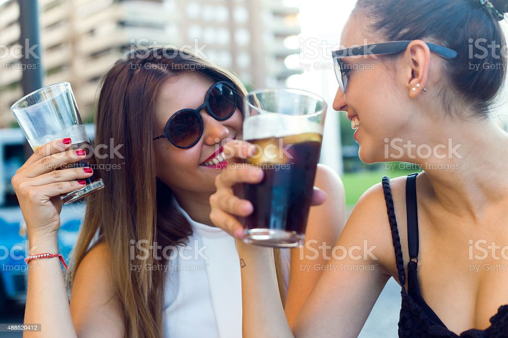 Beautiful young women drinking refreshment in the street. stock photo