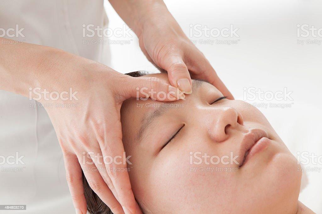 Beautiful young women getting a face massage in massage salon. stock photo
