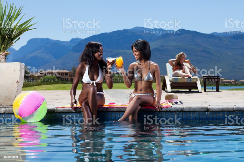 Beautiful Young Women Having Toasting Drinks Outdoors By The Pool royalty-free stock photo