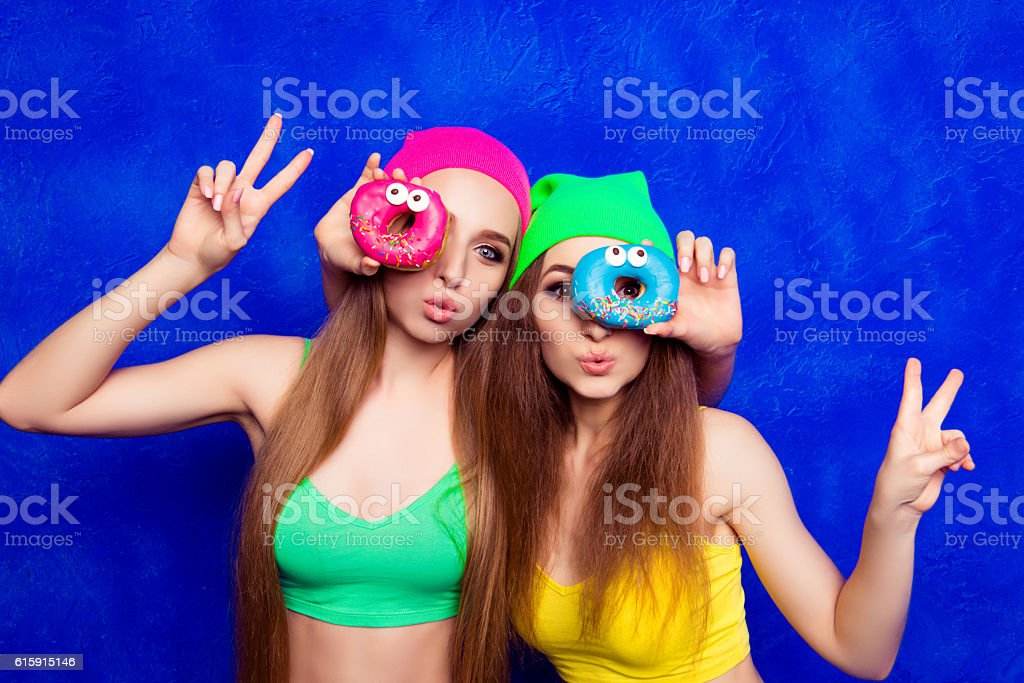 Beautiful young women holding color donutes near eyes stock photo