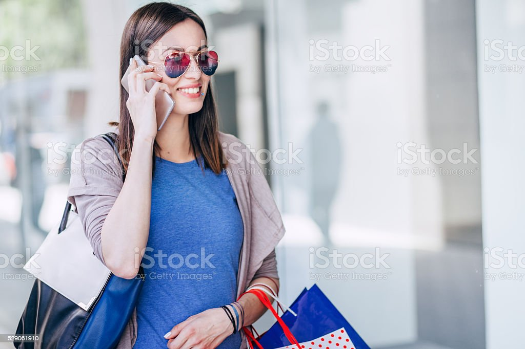 Beautiful young women shopping and using a smart phone stock photo