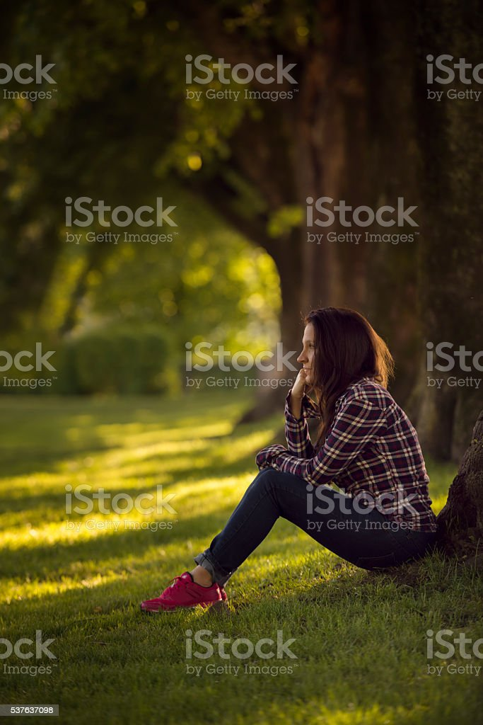 beautiful young women sitting in a park stock photo