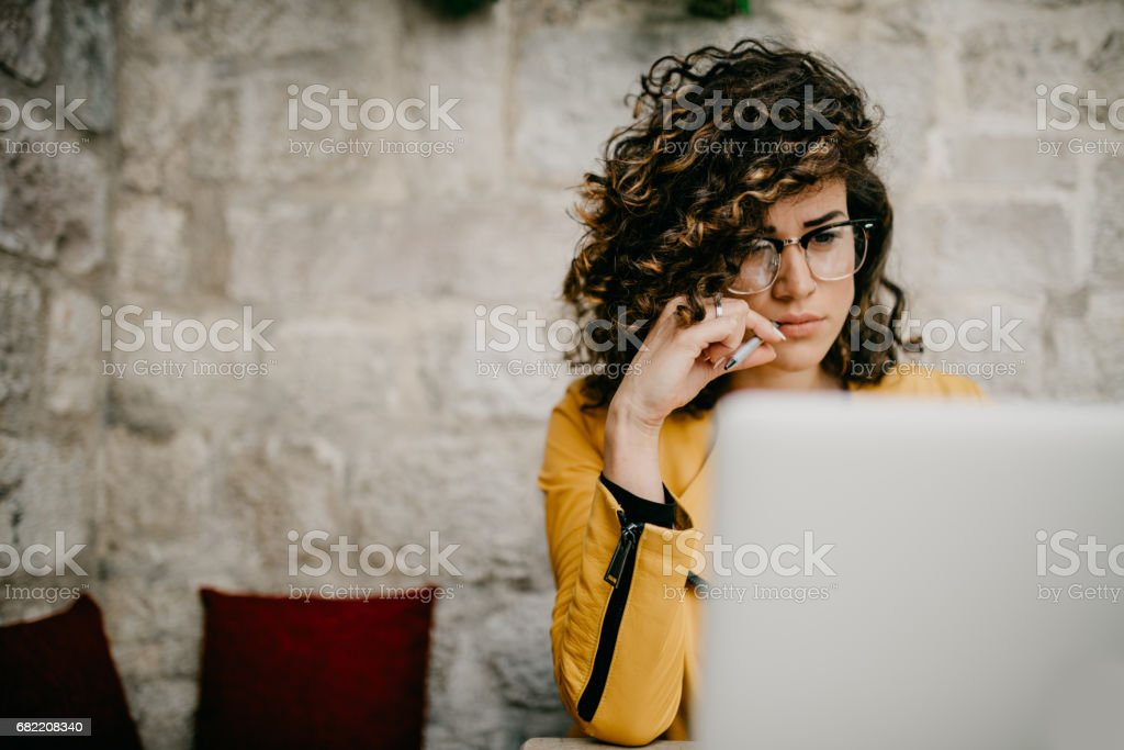Beautiful young writer is doing a research on her laptop stock photo