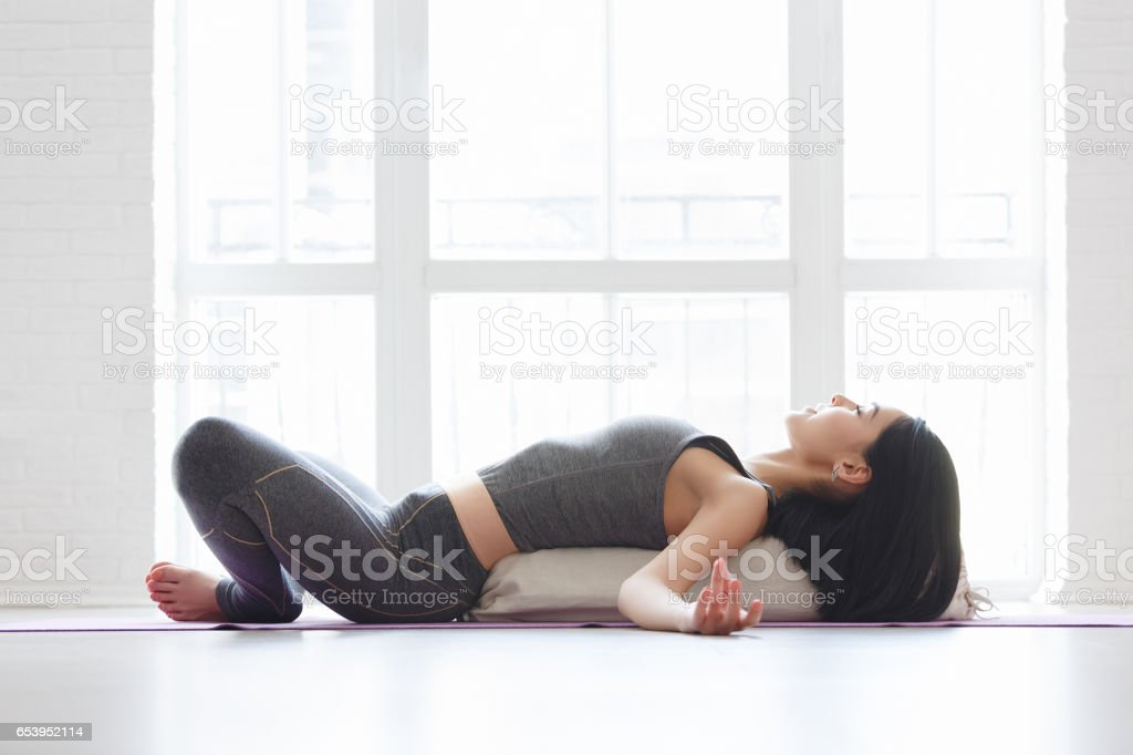 Beautiful young yoga girl lying in asana Shavasana stock photo