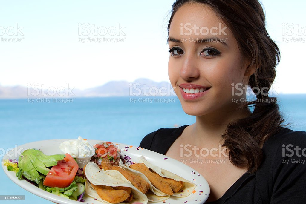 Beautifull Mexican woman serving Fish Tacos royalty-free stock photo