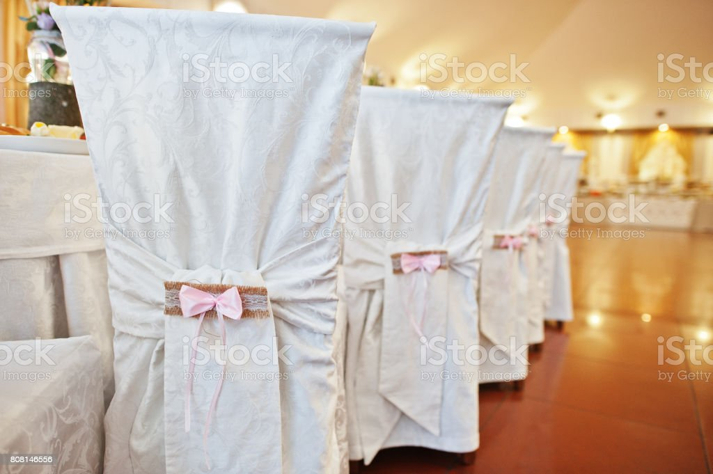 Beautifully decorated restaurant chairs for wedding celebration. stock photo