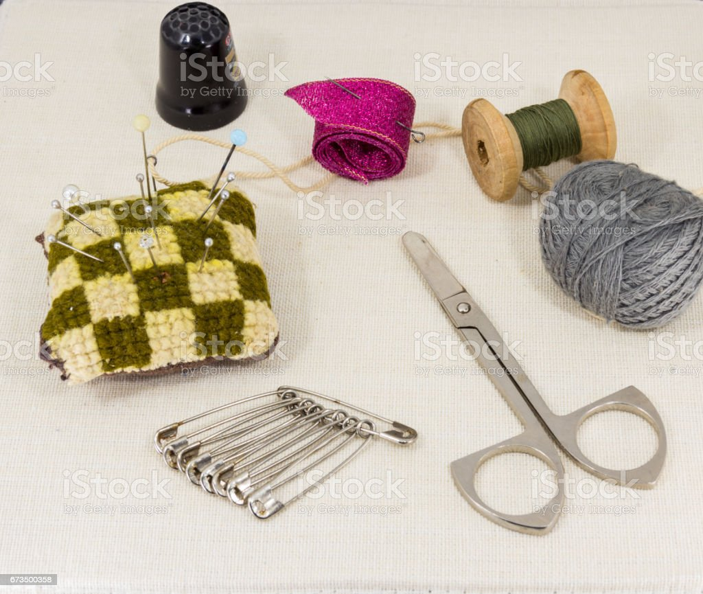 Beautifully laid out accessories for needlework on a fabric background stock photo