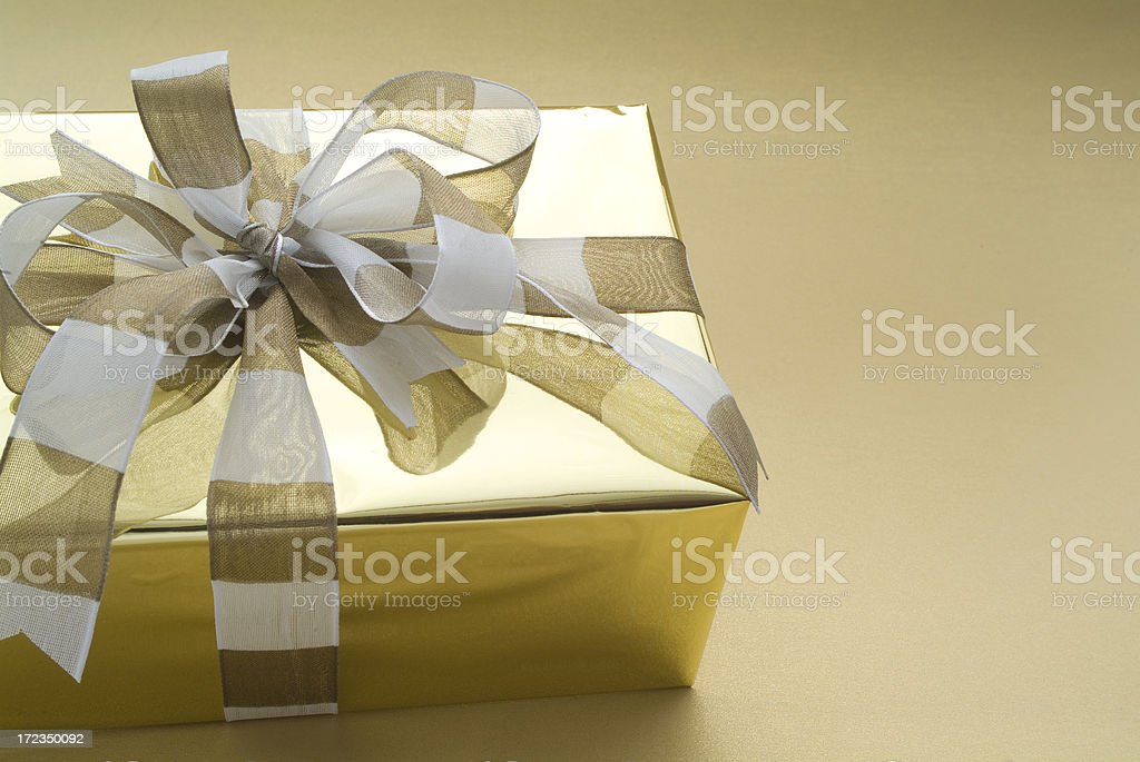 A beautifully wrapped gift in gold  and white royalty-free stock photo