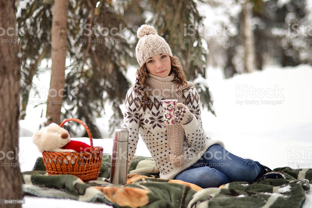Beautiful,smiling girl sit on warm blanket in winter forest stock photo