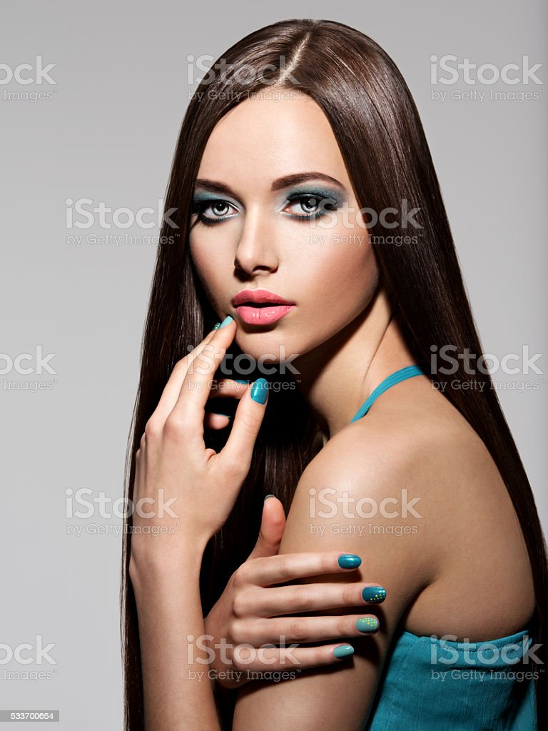 Beautiul elegant woman with turquoise make-up and long hairs stock photo
