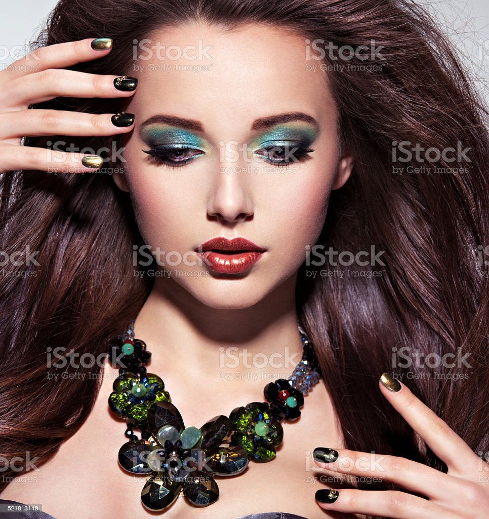 Beautiul  woman with  long brown hairs, turquoise make-up and stock photo