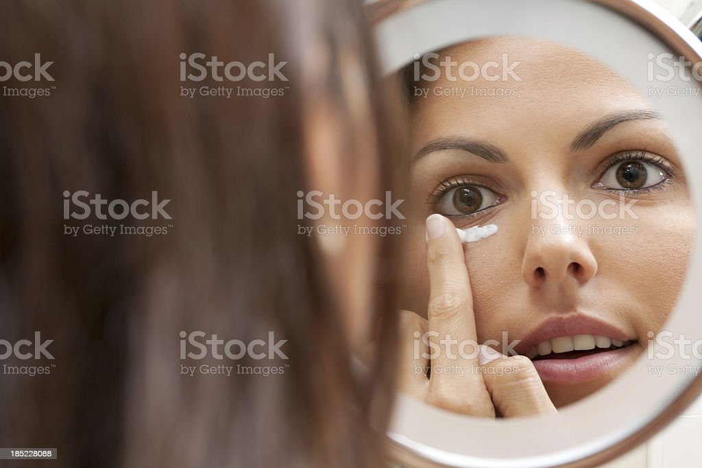 Beauty applying Moisturizer against Wrinkles on her Face royalty-free stock photo