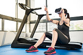 beauty asian woman rest on treadmill with VR headset