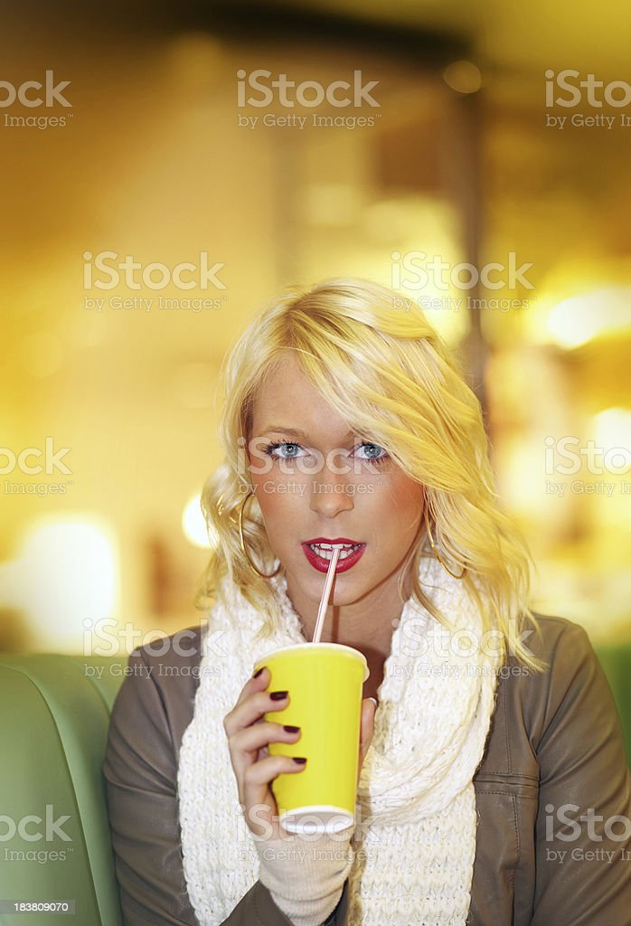 Beauty blond teenager sitting in a shopping center royalty-free stock photo