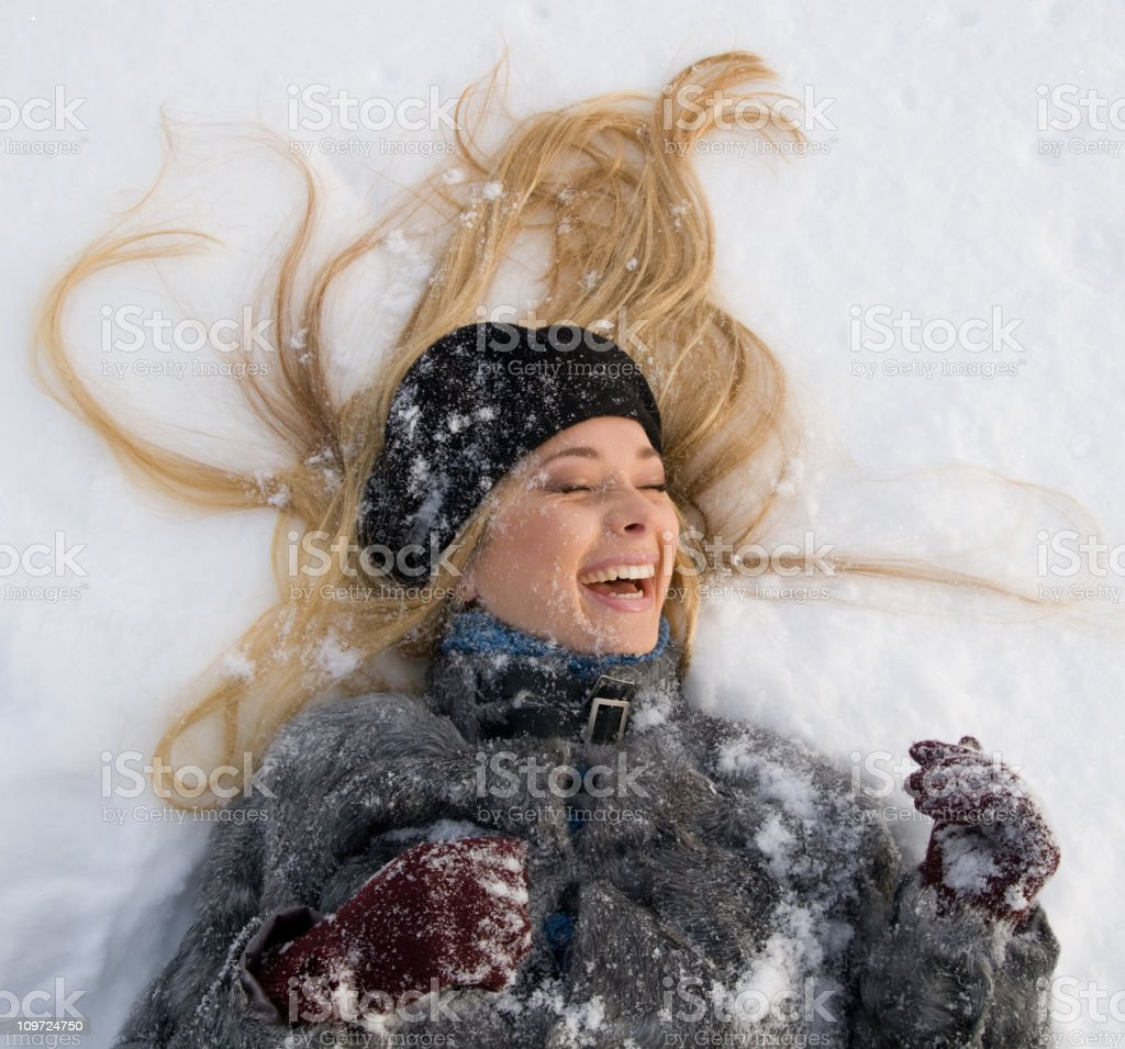 Beauty blonde laying in the snow royalty-free stock photo
