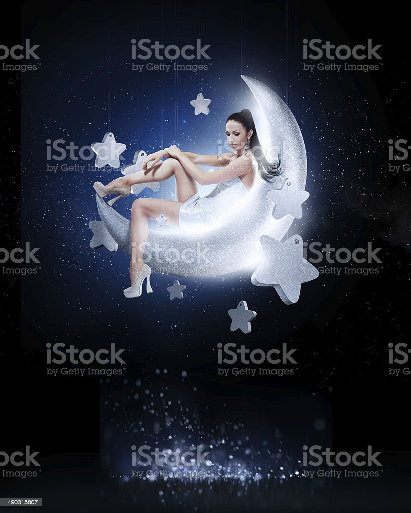 Beauty brunette sitting on the crescent moon stock photo