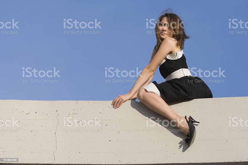 beauty girl sit on concrete billboard royalty-free stock photo