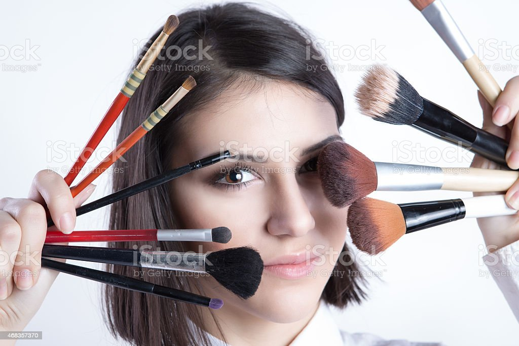 Beauty girl with makeup brushes stock photo