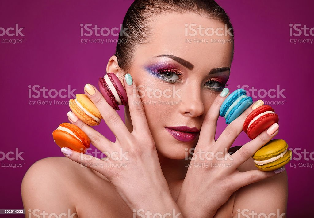 Beauty glamor fashion model girl with colourful makeup and macaroons. stock photo