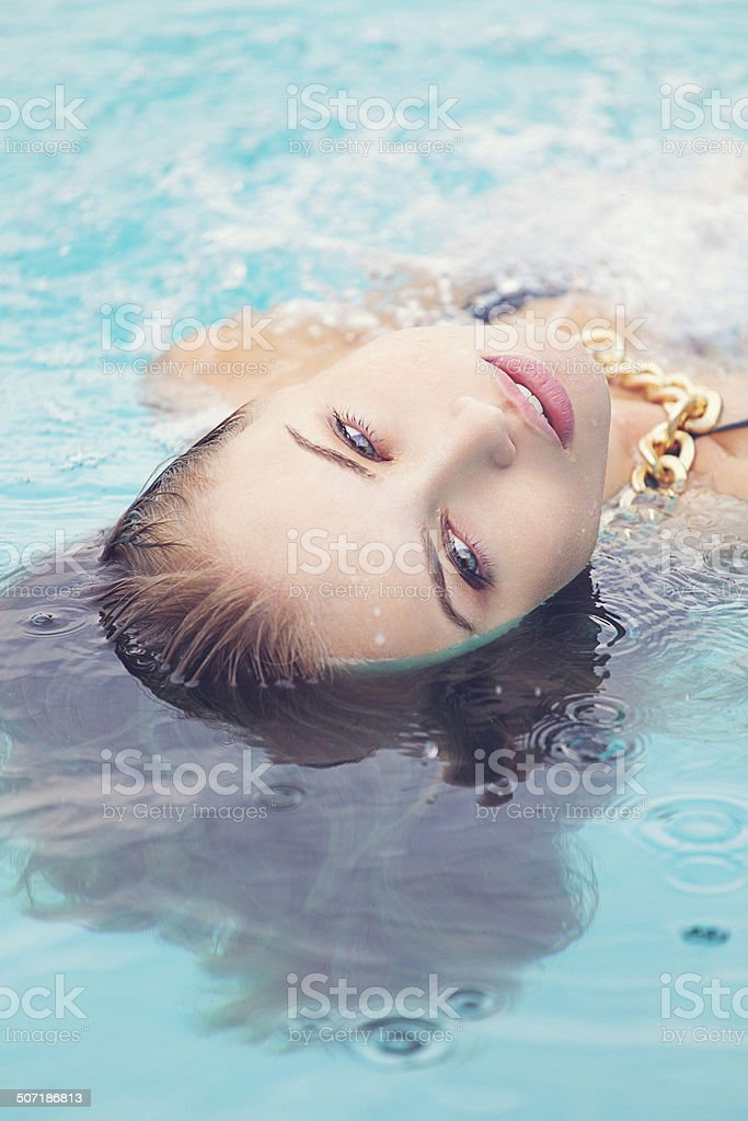 Beauty headshot of a young woman relaxing in the pool royalty-free stock photo