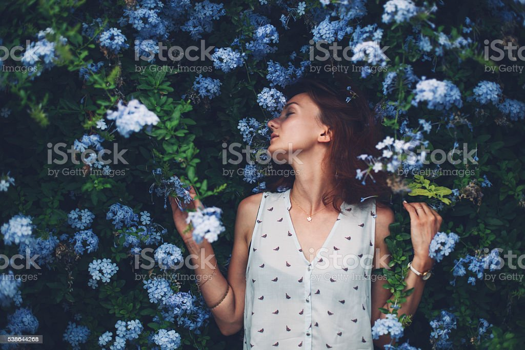 Beauty in Nature. Woman Portrait on flowers background stock photo