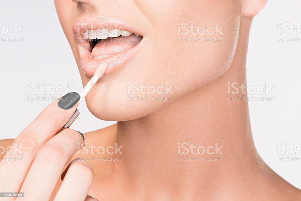 Beauty  Make-up  Women applying lip gloss   Beautiful sensual lips stock photo