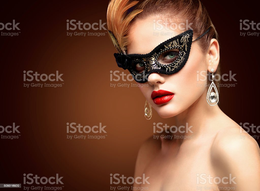 Beauty model woman wearing venetian masquerade carnival mask at party stock photo