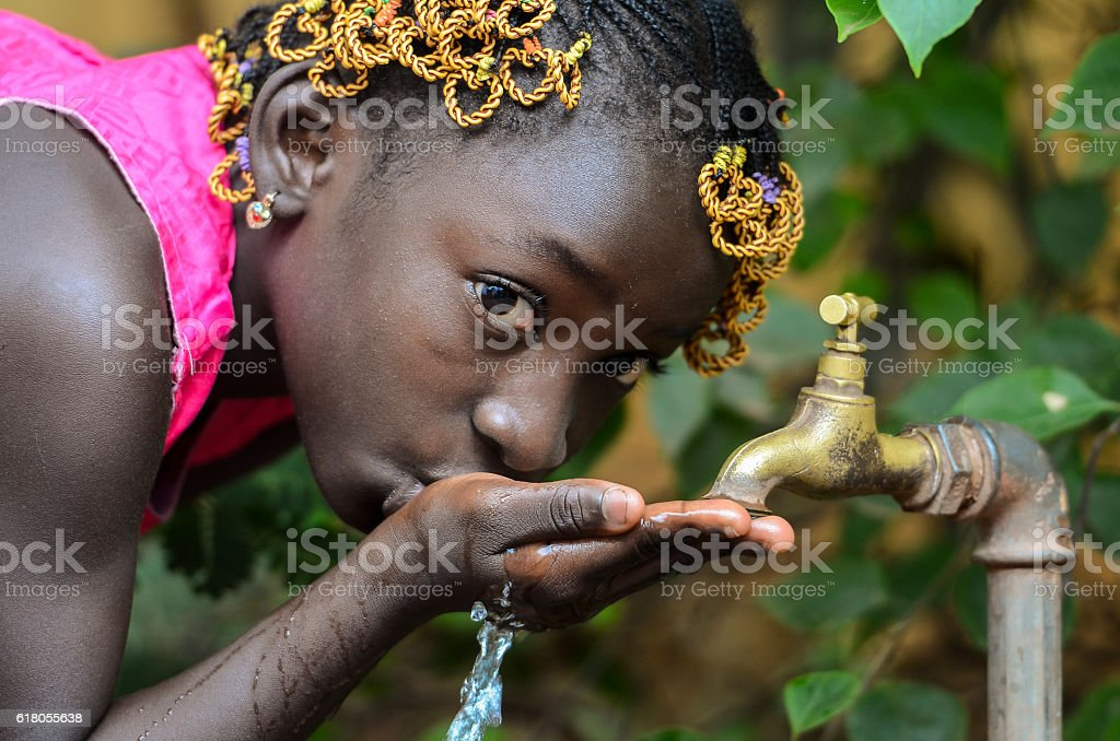Beauty of Africa Drinking Clean Water from a Faucet stock photo