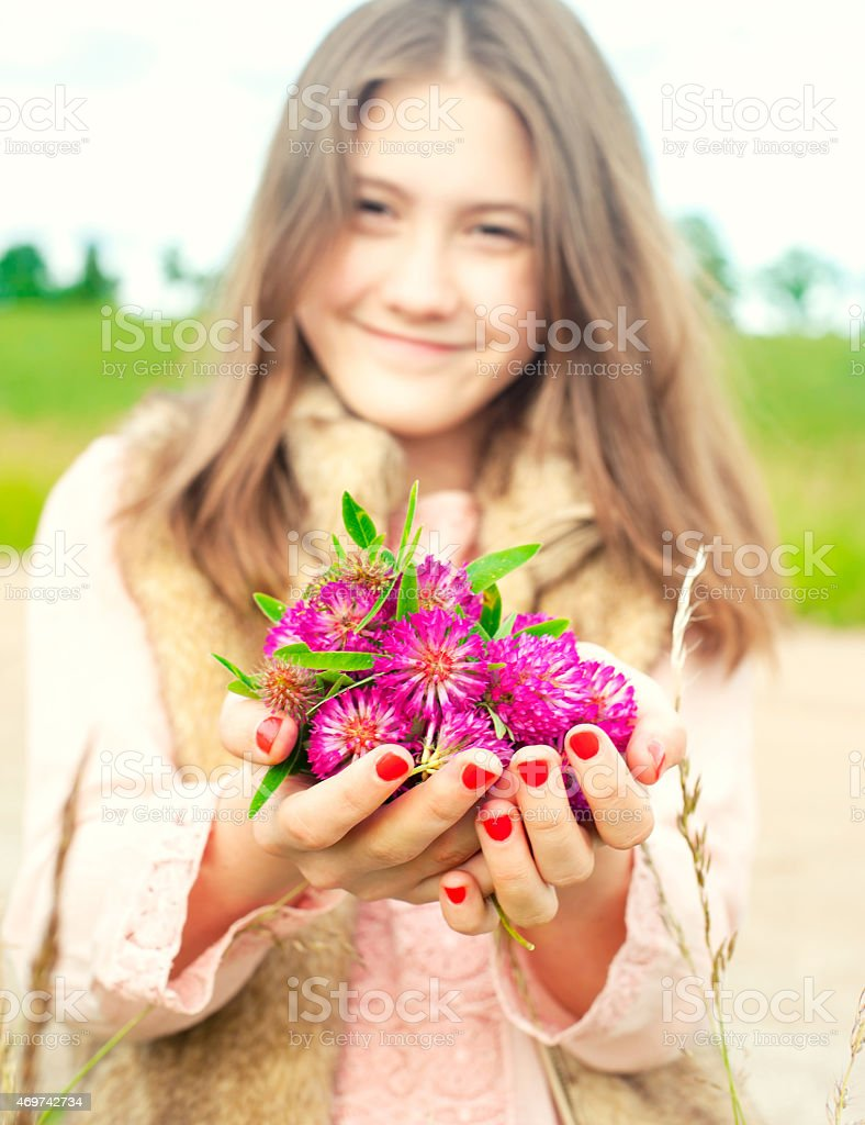 Beauty of nature. Smiling young girl holding meadow clover flowers stock photo