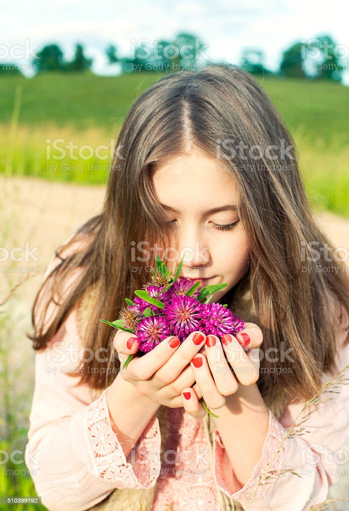 Beauty of nature. Smiling young girl smelling meadow clover flowers stock photo