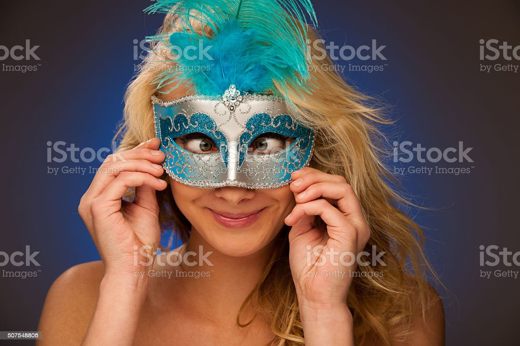 beauty portrait of young blonde woman with venice carnival mask stock photo