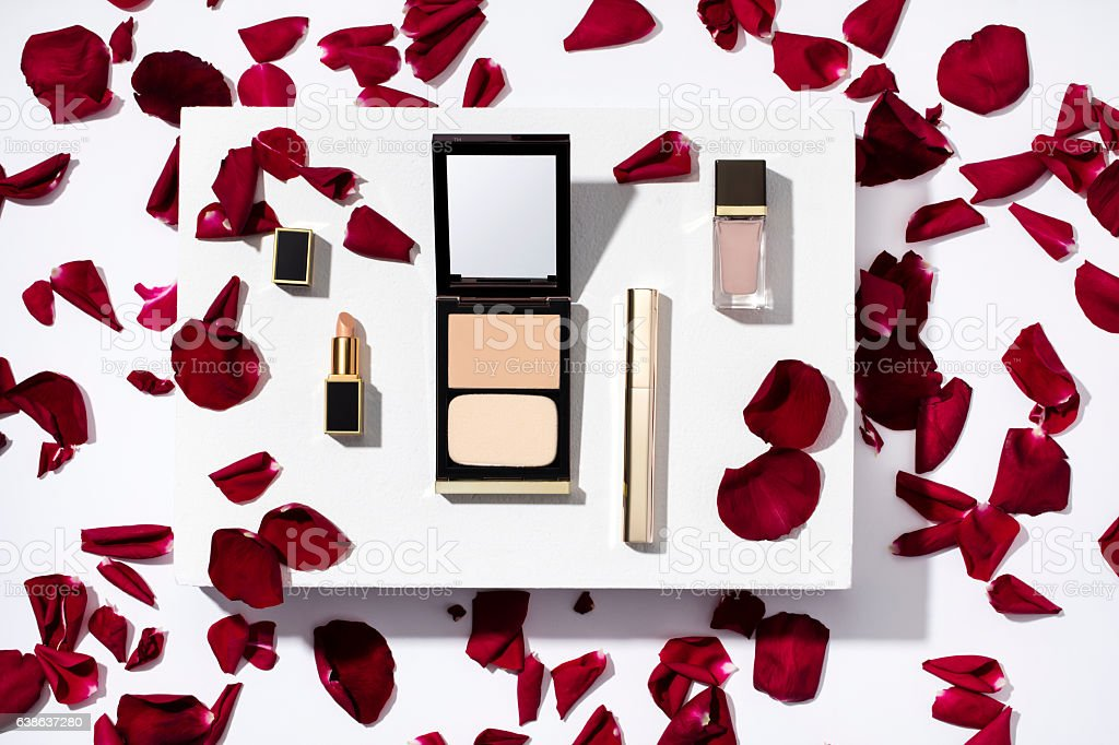 Beauty products with red rose petals on white background