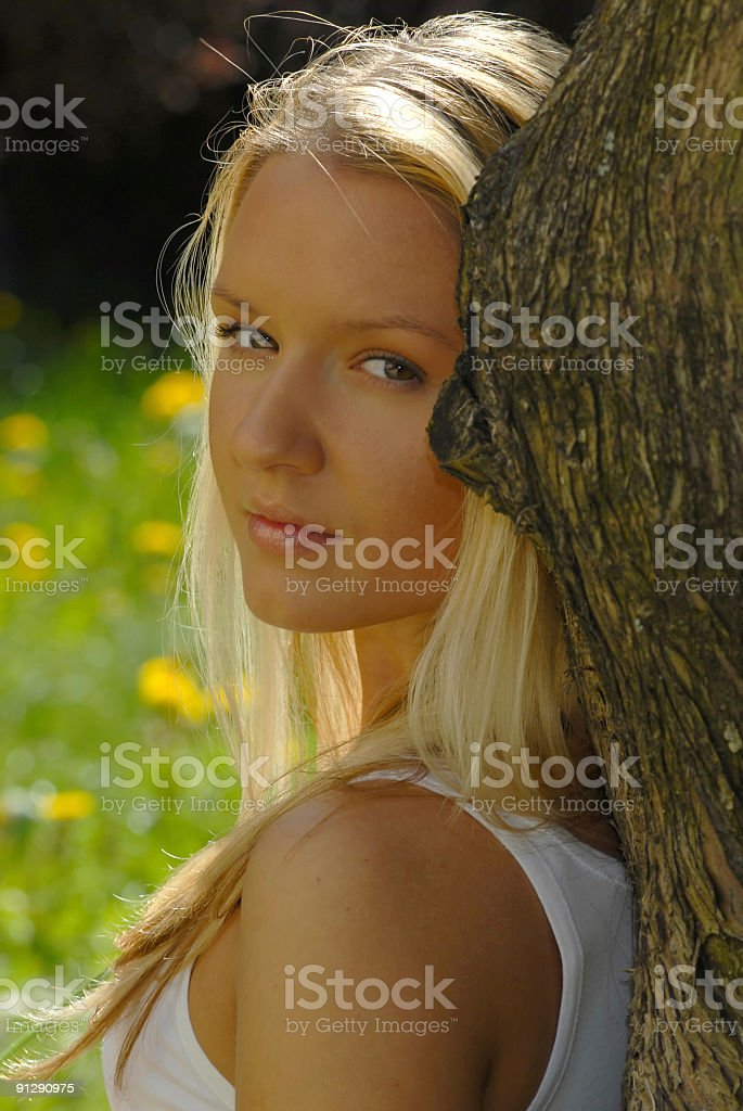 Beauty resting on a tree and watching over the shoulders royalty-free stock photo