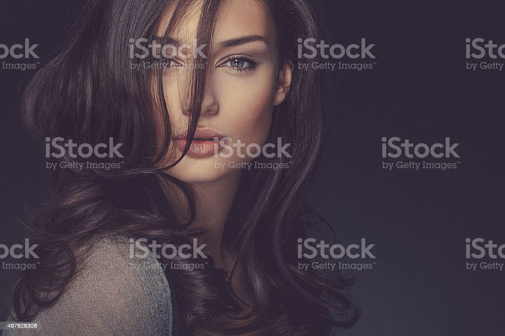 Beauty shot of a smiling long haired, beautiful brunette woman stock photo