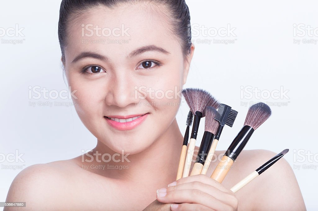Beauty shot of woman holding the makeup brush stock photo