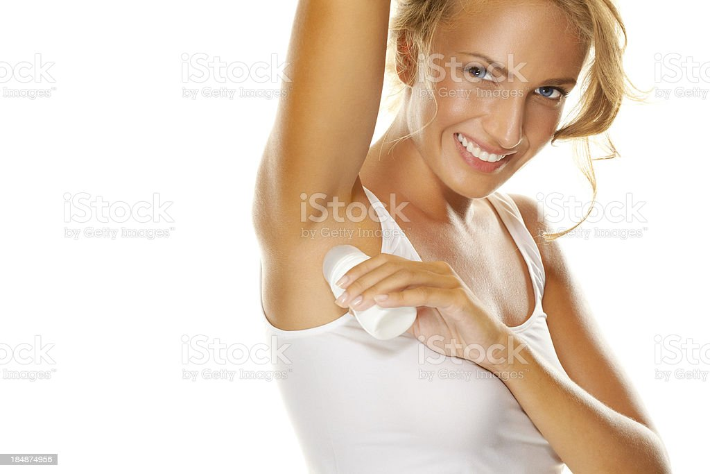 Beauty shot of young, beautiful, blonde woman applying roll-on deodorant stock photo