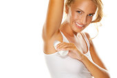 Beauty shot of young, beautiful, blonde woman applying roll-on deodorant