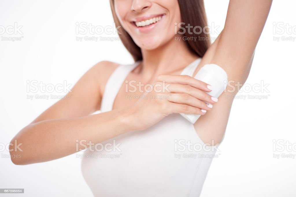 Beauty shot of young beautiful brunette woman applying roll-on deodorant. stock photo