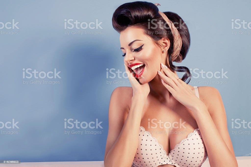 Beauty smiling pinup girl on blue wall stock photo