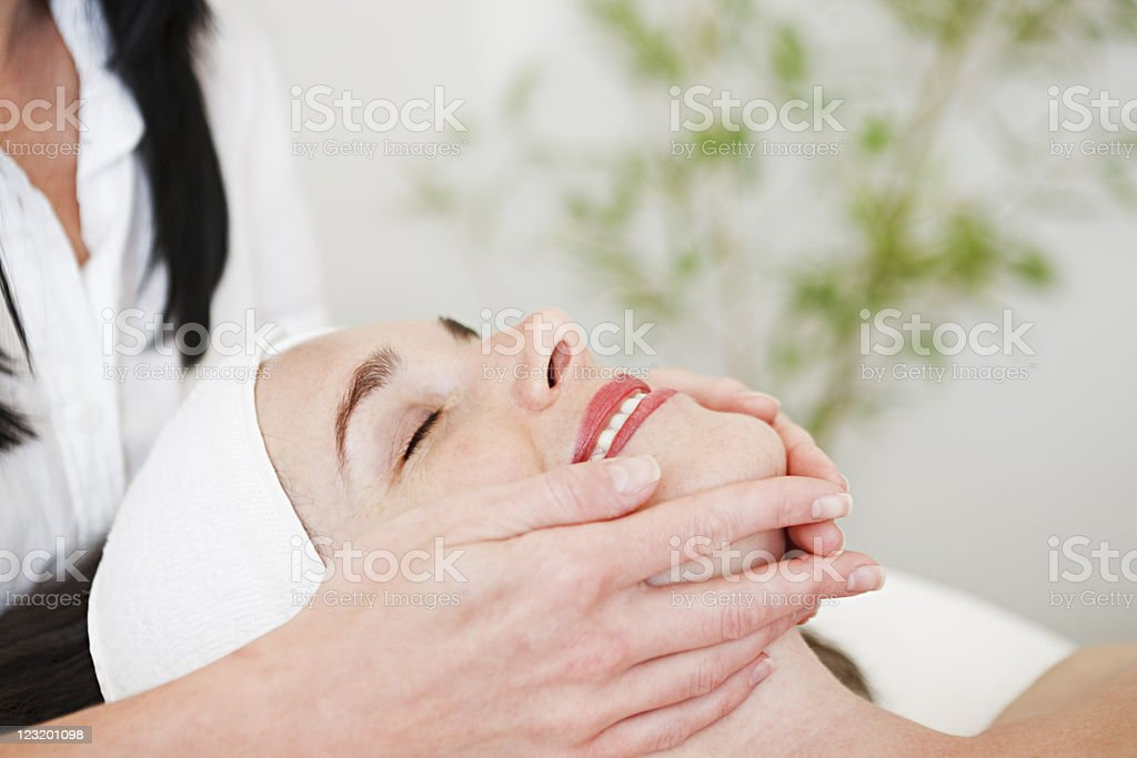 Beauty therapist gives face massage stock photo