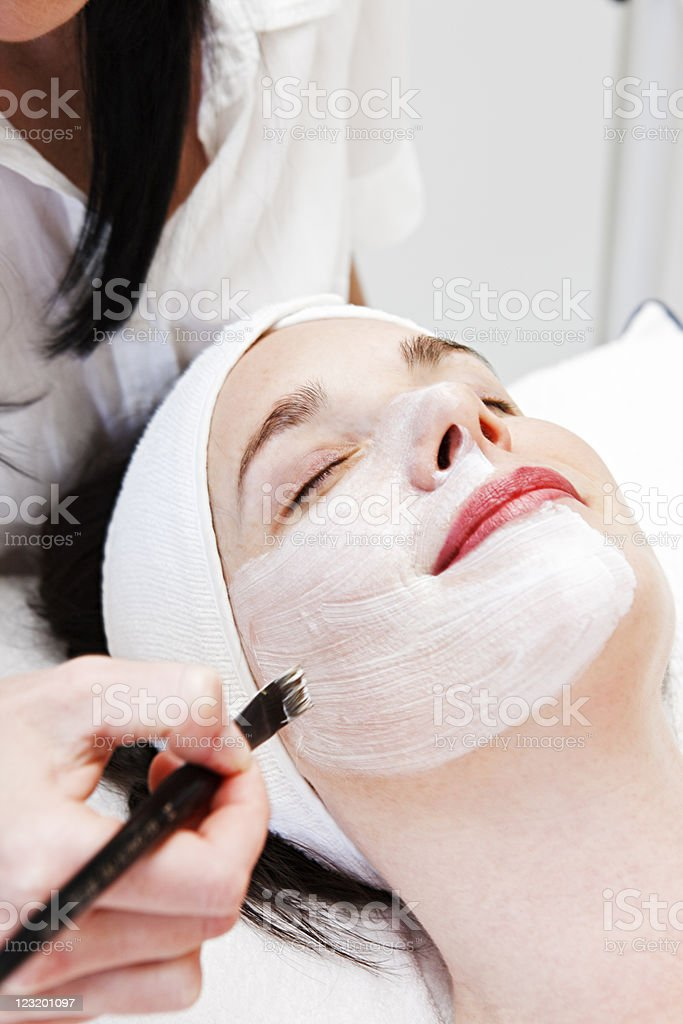 Beauty therapist paints facial mask royalty-free stock photo
