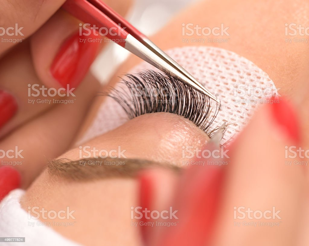 beauty treatment, applying false eyelashes stock photo