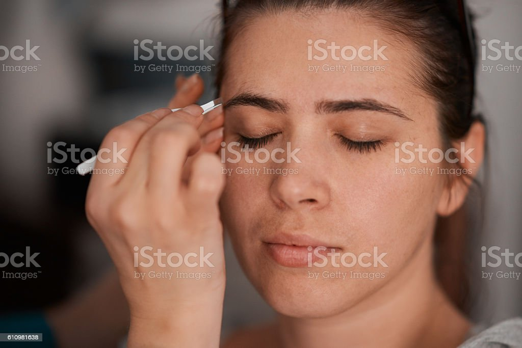 beauty treatment at salon,plucking eyebrow stock photo