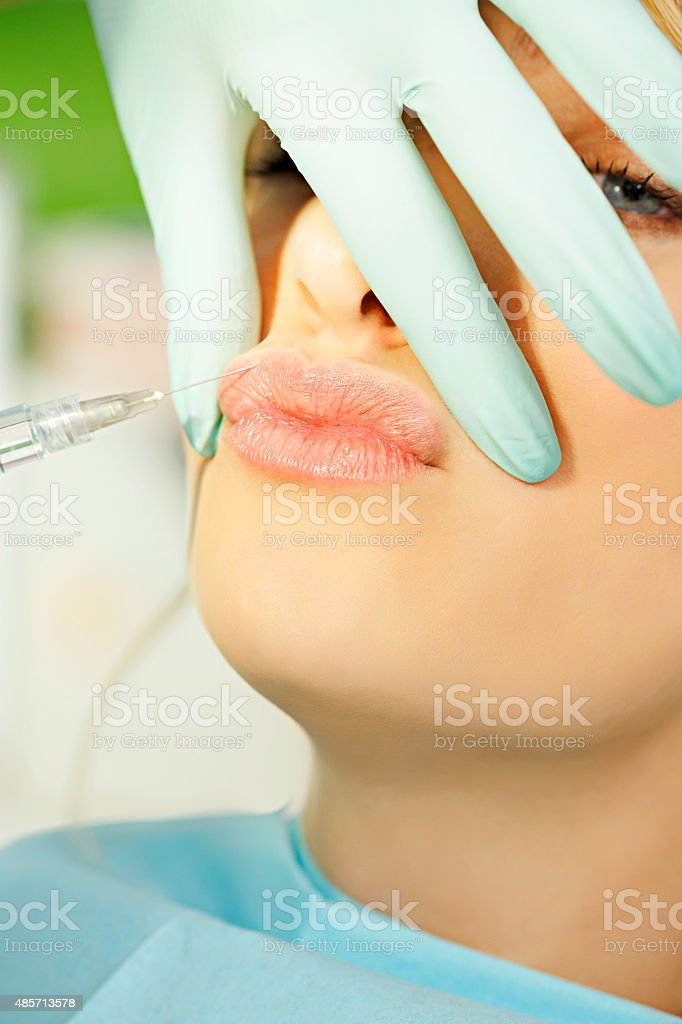 Beauty treatment  Beautiful blonde having cosmetic injection in the lips stock photo