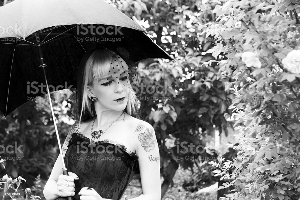 Beauty with umbrella considers roses, B&W. royalty-free stock photo