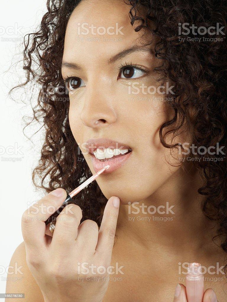 Beauty woman applying lip gloss smiling royalty-free stock photo