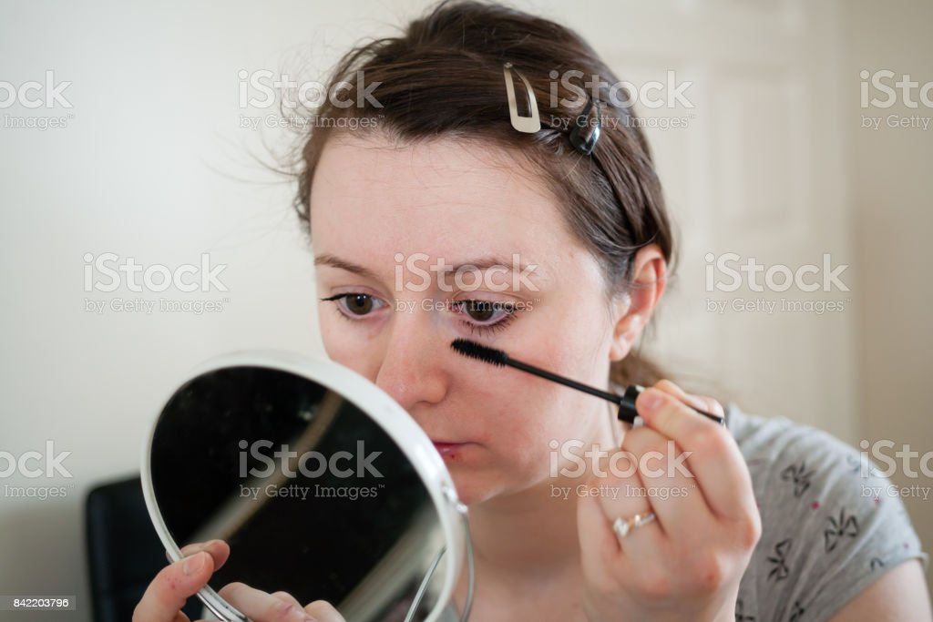Beauty woman applying makeup on the eyebrows. Beautiful girl looking in the mirror and applying cosmetic with a eye brush. stock photo