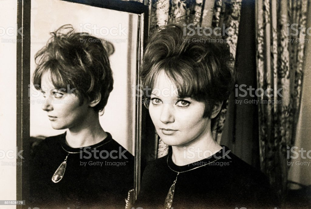 Beauty woman from the sixties infront of a mirror stock photo